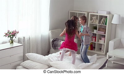 Group of kids holding hands and enjoying jumping on the bed