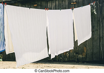 Bed linen are airing - Washed bed linen hanging on rope and ...