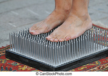 Fakir foots standing on a nails bed