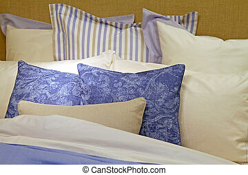 Cotton bed sheets with big pile of pillows