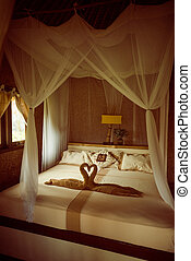 Bed with canopy and swans made of towels in bungalow