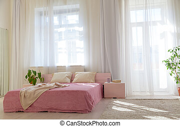 bed with pink sheets in a white room with plants