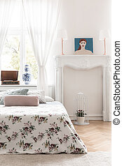 Bed with rose decorated cover and an ornamented fireplace mantel in a high ceiling vintage bedroom interior. Real photo.