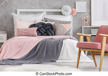 Bed with soft color bedsheets - Pastel pompons on bolster of...