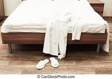 Bed with white linens and white bathrobe with slippers in hotel