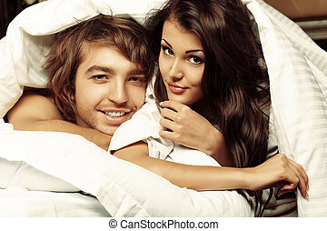 bedclothes - Young woman and a man in love lying in a bed.