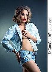 beddable, mulher jovem, posar, em, calças brim, roupas