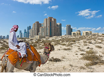Bedouin on a camel in the desert and a modern city on the ...