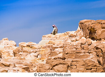 Bedouin sitting on the peak of a high stone rock against a blue sky in Egypt Dahab South Sinai