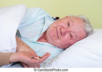 Picture of a bedridden elderly patient receiving his pills