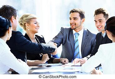 bedrijfscollega's, zitting op een tafel, gedurende, een, vergadering, met, twee, mannelijke , stafmedewerkers, schuddende handen