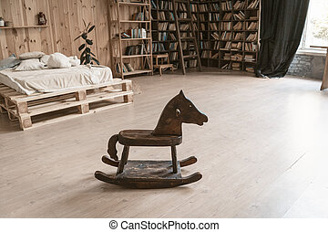 Bedroom in a wooden interior. In the foreground is a wooden horse. In the background is a bed and a bookshelf. High quality photo
