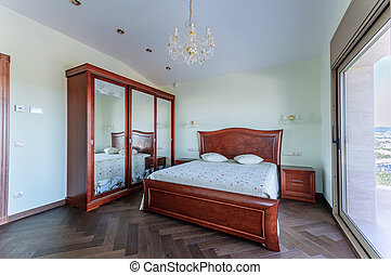 Bedroom in classic style.  Luxury mahogany furniture. Wardrobe with mirrors.