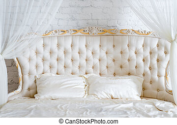 Bedroom in soft light colors. Big comfortable double bed in elegant classic bedroom. Luxury elegant white with gold interior design.
