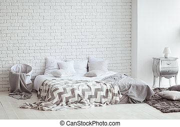 Bedroom interior with a brick wall with a bed and bedside tables.
