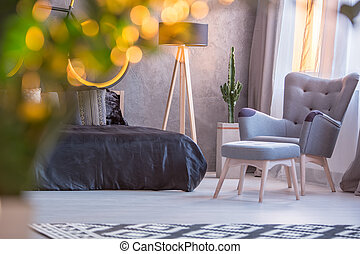 Grey bedroom with black bed, armchair and footstool