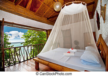 Bedroom with canopy bed with sea view