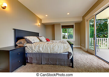 Bedroom with carpet and large balcony door.