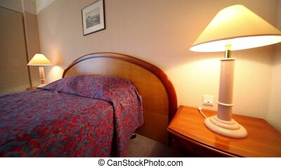 Bedroom with lamps on each side of bed and pair of armchairs at table, tv set near mirror