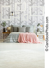 Copy space photo of bedroom interior with black and white forest wallpaper, pink blanket and striped bedsheets