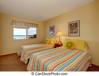 Light tone bedroom with two single beds in cheerful striped bedding with yellow pillows