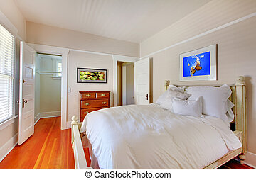 Bedroom with white bed and cherry hardwood floor.