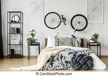 Black and white bedsheets with floral motif on king-size bed with bike on bedhead