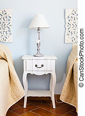 a luxurious bedroom with a lamp over a bed side table