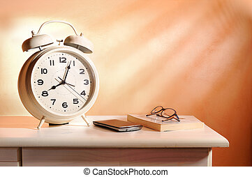 bedside alarm clock and personal belongings in the morning