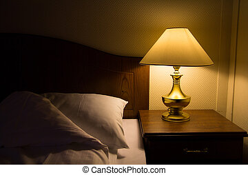 Bedside at night - Lamp on a night table next to a bed