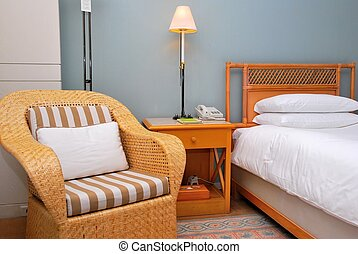 Chair at bedside in a high class hotel room. Suitable for concepts such as business and executive travel, tourism, vacation and holiday, and relaxation.