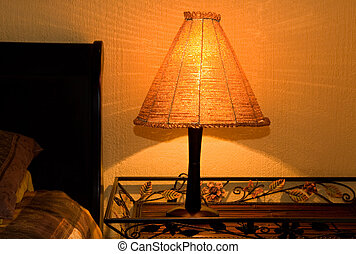 bedside lamp made from orange african glass beads on bedside tray casting a warm glowing light