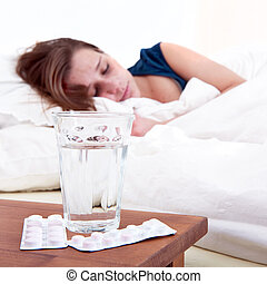 Bedside pills - Glass of water and two strips of pills on a ...
