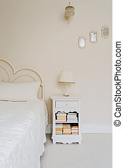 Bedside table with shelves for books in bedroom