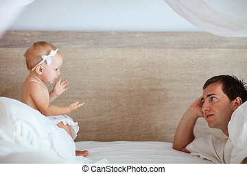 Bedtime - Young father and cute baby girl talking with each ...