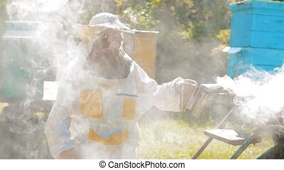 bee-maker beekeeper man working of a smoke pipe beeper...