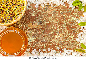 Bee pollen an honey on a wooden background