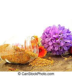 Bee pollen copy space - Bee pollen in glass jar and flowers...