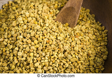 Bee pollen in wooden scoop. Nutritional supplement