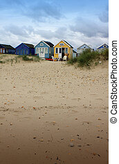 Beech Hut and Sand - A row of wooden colorfully painted...