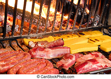 beef and pork cooked on the grill in the glowing embers of...