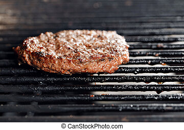 Beef Burger And Spatula On The Hot Flaming BBQ Charcoal Grill, Close-up