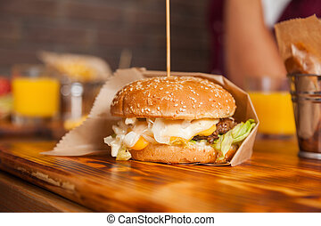 Beef Burger Served In Paper On Wooden Table