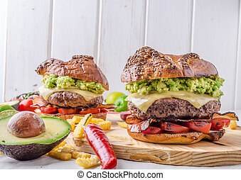 Beef burger with avocado dip and baked tomato