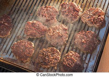 Beef burgers being grilled on barbecue.