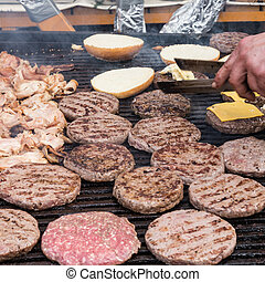 Beef burgers being grilled on food stall grill.