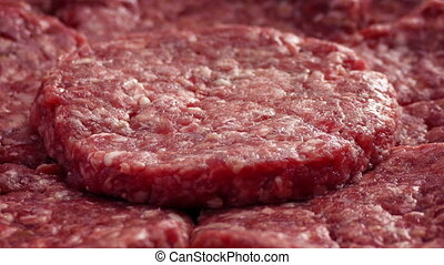 Beef Burgers Rotating - Closeup of mince meat beef burgers...