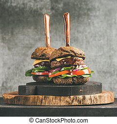 Beef burgers with barbeque sauce on wooden boards, square crop