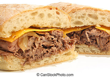 Beef dip sandwich with cheese and au jus.