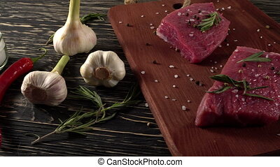 Beef fillet on a desk with pepper, rosemary and garlic. -...